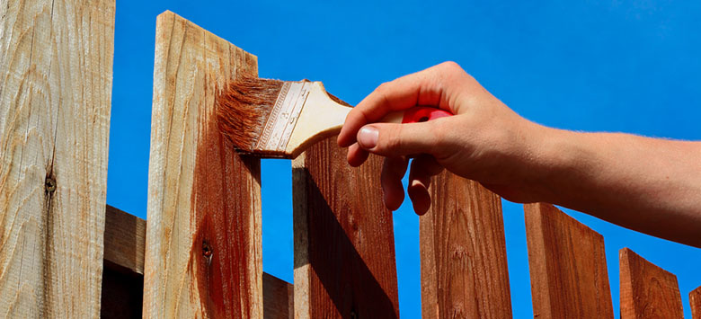 Man painting a fence.