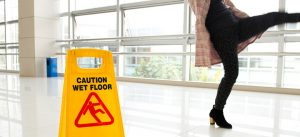 Woman slipping next to a sign.