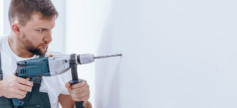 Man drilling in plaster wall.