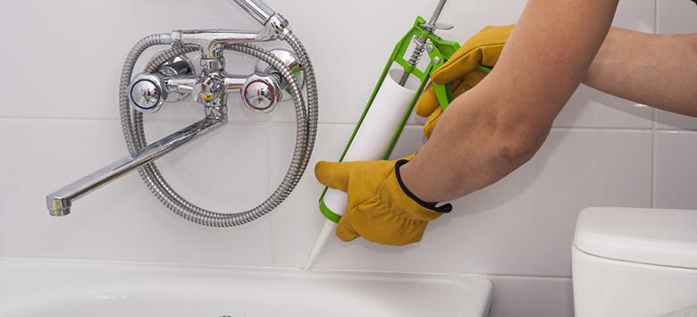 Man applying caulk to a bathtub.
