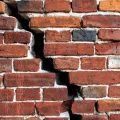Huge vertical crack on a brick wall.